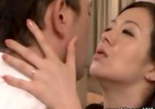 mature oriental milf giving a kiss with voyeur